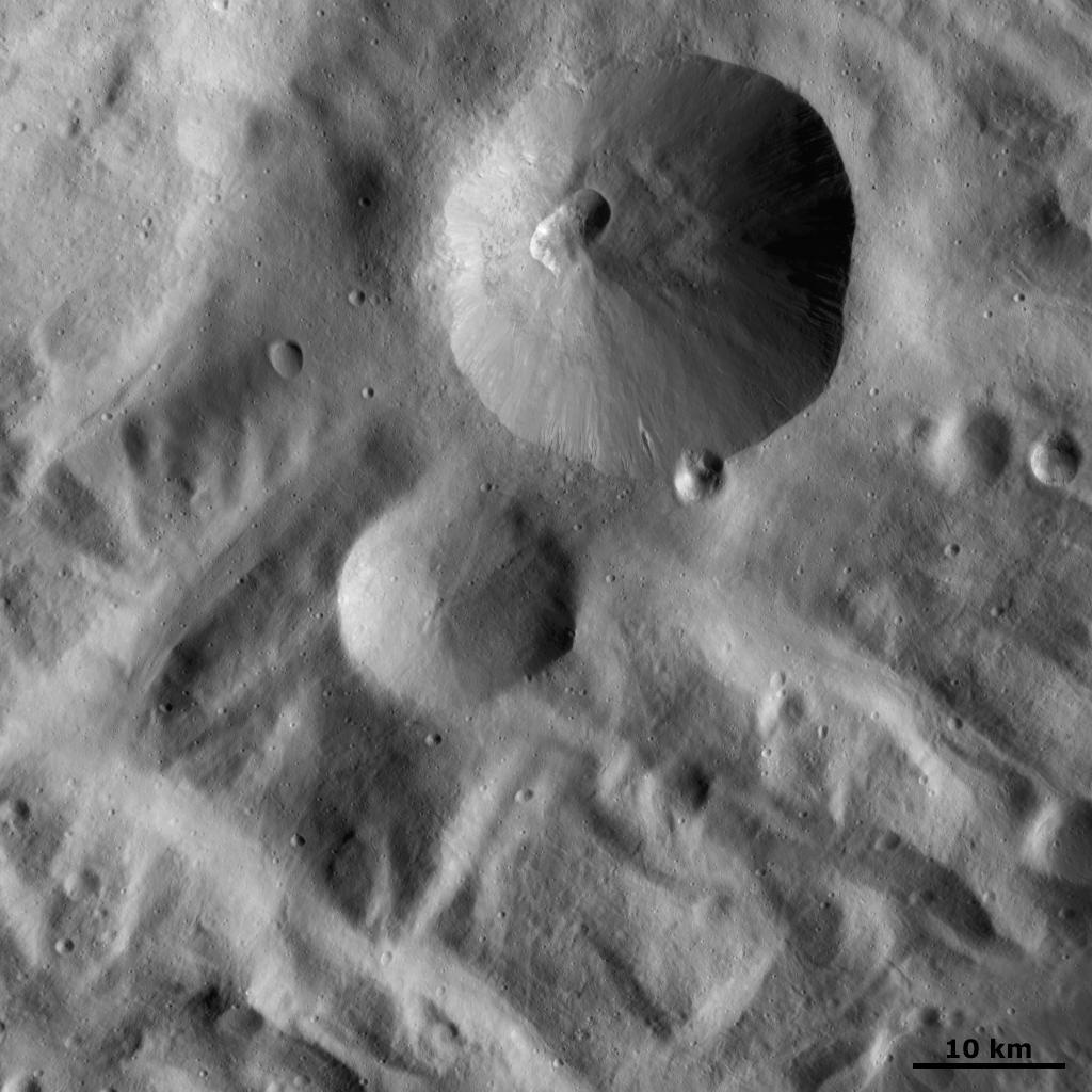 Severina Crater This image shows Severina crater. This is the large crater, approximately 25 kilometers (15 miles) in diameter, visible at the top of the image. Severina crater has a fresh, sharp rim and a smaller, presumably younger, crater on its rim. There is an interestingly shaped small crater within Severina. This crater is roughly rectangular in shape, possibly because it is the result of two craters merging together or possibly because it is the result of erosion and slumping of one crater. This image is located in Vesta's Rheasilvia quadrangle, near Vesta's south pole. NASA's Dawn spacecraft obtained this image with its framing camera on Oct. 22, 2011 from a distance of 700 kilometers (435 miles).