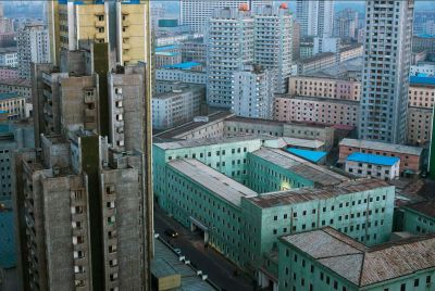 "Central Pyongyang At Dusk The New York Times' Lens blog profiles David Guttenfelder, an AP photographer who is the only Westerner able to shoot in North Korea on a regular basis. Guttenfelder's work is a part of ""Window on North Korea,"" a photography exhibit taking place in New York City that places images by AP photographers next to those taken by Korea State Media (KCNA) photographers. Via the New York Times:  [The show] has some of the best of the North Korea images by Mr. Guttenfelder and his A.P. colleagues. But the photos by the KCNA are most telling. They are highly idealized images: everyone is well fed, and smiling. The workers are heroic and the leaders have a heavenly glow.  There are no traces of the hunger, hardships and repression that exist in North Korea. They may be propaganda but they do provide insight into how the North Korean government officials want — and need — their people to see their country.  A slideshow of images from the exhibit is available at the Lens blog. Image: Central Pyongyang At Dusk by David Guttenfelder, AP. Via the New York Times."