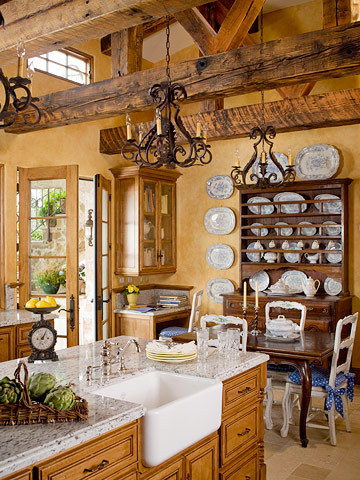 Although this kitchen has a 17-foot-high ceiling, beams from an old railroad bridge make it feel cozy. The homeowners used wood cabinetry and dark furnishings to complement the rustic beams. (via Vaulted Ceiling Kitchen Ideas)