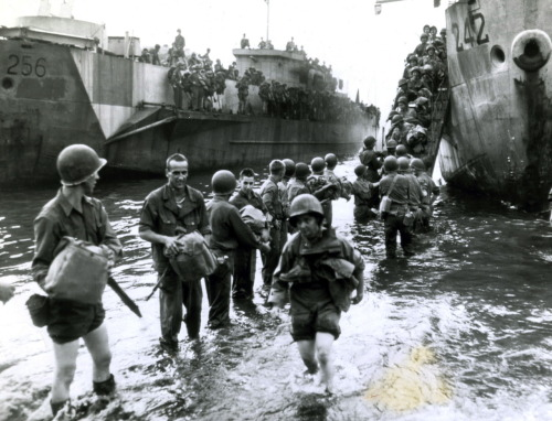 While Navy sailors transport gear from their landing craft to shore, an Army nurse wades ashore with her G.I. shoes slung around her neck and her coveralls rolled above her knees. Naples Harbor, Italy. 11/5/45
