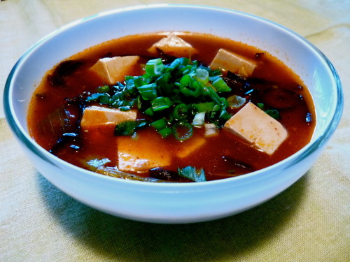 Hot and Sour Soup This is my recipe for hot and sour soup and it is absolutely delicious. I recommend making this with chicken stock and strips of chicken or pork and an egg as well. To add an egg to the soup, beat the egg in a bowl and stir into soup in a thin stream right before the last step of adding in the sesame oil. Chinkiang vinegar is a fragrant Chinese black vinegar that is easily found at an Asian grocery store. Sichuan peppercorns have a numbing effect on the mouth that some find undesirable but in its whole form have a scent reminiscent of black pepper, lavender and peppermint.  Serves 4 Ingredients: 1 tbsp vegetable oil 2 tbsp chopped garlic 2 tbsp chopped ginger 2 tbsp Korean hot pepper flakes  1/2 cup thinly sliced shiitake mushrooms 1 cup dried thinly sliced wood ear mushrooms, soaked in warm water 1/2 cup thinly sliced bamboo shoots 6 cups vegetable stock (I used Better than Bouillon mushroom base) 1 block extra firm silken tofu, cut into 3/4 inch cubes 2 tbsp rice wine vinegar Chinkiang vinegar (I use Chundan brand) 2 1/2 tbsp soy sauce large pinch of sugar 1 tsp ground black pepper 1 tsp ground Sichuan peppercorns (optional) 5 scallions, 4 chopped into 1 inch pieces and 1 finely chopped for garnish 3 tbsp corn starch 1 tablespoon sesame oil Method: Heat vegetable oil in a stock pot over medium. Add in chopped ginger and garlic and stir for 1 minute until fragrant. Add in hot pepper flakes and continue cooking for another minute. Add in shiitakes, wood ear mushrooms and bamboo shoots. Cook for about 3 minutes, stirring constantly. Add in vegetable stock and bring to a boil. Reduce heat, cover and let soup simmer for 10 minutes. After 10 minutes, stir in the 1 inch pieces of scallion, vinegars, soy sauce, sugar, black pepper, Sichuan peppercorns and tofu. Cover and simmer again for 10 minutes more. Mix together 3 tbsp cornstarch and 3 tbsp water. Slowly pour this mixture in a circular motion into the soup while stirring gently. Be careful not to break up the tofu cubes. Simmer for about 5 minutes or until the soup thickens. Stir in the sesame oil. Serve hot, garnished with the reserved chopped scallion.