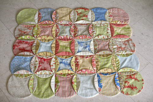 "Here is my faux cathedral window baby play mat more or less finished. I still have to sew most of the flaps down - but I remain unconvinced and have lost motivation to finish it. It's one of those ""don't look too closely"" quilts. As it is meant to be a gift, I think I should probably make something else. Note to self: Don't try completely new techniques when making gifts."