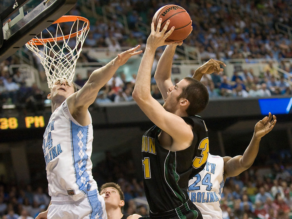 UVM forward Clancy Rug shoots over UNC's Tyler Zeller to score in the Catamount's final NCAA tournament game Friday night, March 16, 2012, at the Greensboro Coliseum in North Carolina. http://bfpne.ws/yHVsmX  (Photo by RYAN MERCER, Free Press)