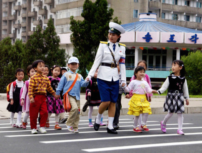 5/6 A traffic officer leads school children across a street in Pyongyang. courtesy Korean Central News Agency
