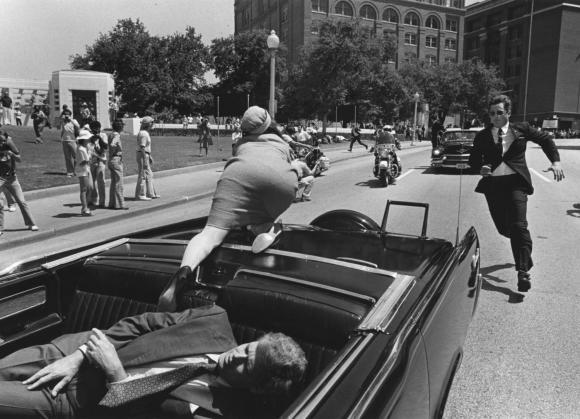 cosmosonic:  John F. Kennedy Assassination Reenactment in Houston, TX Secret Service agent Clinton Hill (stuntman Larry Hill) rushes to get Jacqueline Kennedy (actress Christine Rose) back into the car after her husband President John F. Kennedy (actor Don Gazzaway) was shot by an assassin. The action was all part of a made for TV reenactment movie being filmed in Dallas http://www.upi.com/