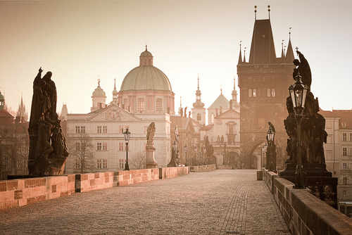 The streets of Prague were a fantasia scarcely touched by the twenty-first century—or the twentieth or nineteenth, for that matter. It was a city of alchemists and dreamers, its medieval cobbles once trod by golems, mystics, invading armies. Tall houses glowed goldenrod and carmine and eggshell blue, embellished with Rococo plasterwork and capped in roofs of uniform red. Baroque cupolas were the soft green of antique copper, and Gothic steeples stood ready to impale fallen angels. The wind carried the memory of magic, revolution, violins, and the cobbled lanes meandered like creeks. Thugs wore Motzart wigs and pushed chamber music on street corners, and marionettes hung in windows, making the whole city seem like a theater with unseen puppeteers crouched behind velvet. ~ Laini Taylor, Daughter of Smoke and Bone