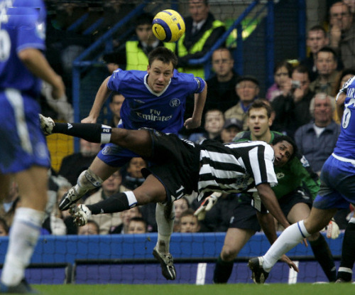 Chelsea's captain John Terry headers the ball away from Newcastle United's Patrick Kluivert during their English Premier League soccer match at Stamford Bridge in London December 4, 2004. Chelsea won 4-0.