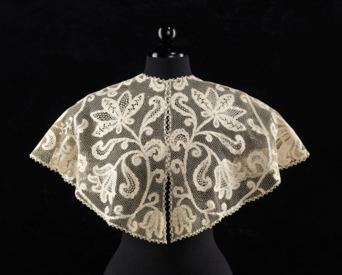 "Italian Lace Collar 1890 The Metropolitan Museum of Art ""Collars this size have a strong presence and this scale is a good vehicle for large and dramatic lace designs such as this one. Notable in the design are the realistic depictions of four different flower varieties, including iris and tulips and the significant variation of grounds in the floral motifs which heightens the visual interest.""    Laces composed of premade tapes such as this one were a less expensive version of their bobbin or needle-made counterparts, in this case Milanese type."