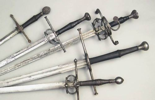 Swords In order from top to bottom:  1. Thrusting Sword, German ca. 1550, pommel and quillon with burled decor.  2. Hand and a Half Sword, German ca. 1520, with blade inscription and crucifix.  3. Hand and a Half Sword, German ca. 1530, flower-bud shaped pommel and quillon ends, the blade with smith's markings of JOHANNES HOPPE, Solingen.  4. Battle Sword, German ca. 1600, the blade with imperial orb marks.  5. Hand and a Half Sword, German ca. 1580, the blade with smith's marks  Source: Image and description Copyright Fricker Historical Weapons