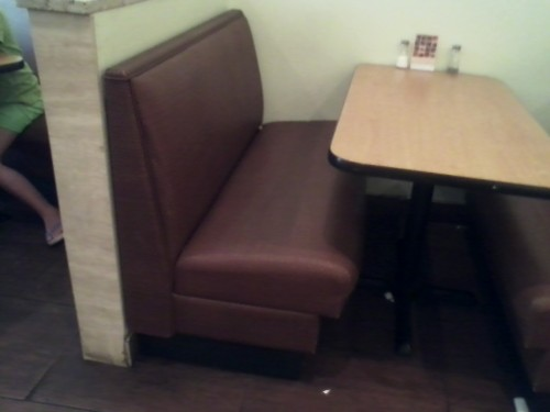 This inviting booth is brown.