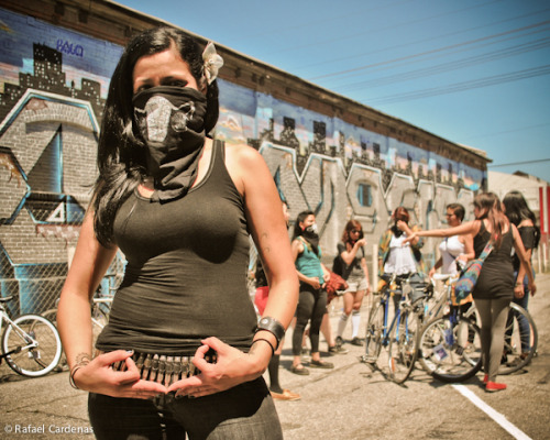 "velvetvivisection:  The Ovarian-Psycos Bicycle Brigade is a all-women bicycle group based out of the Eastside. Xela de la X of the Ovarian-Psycos Bicycle Brigade throws up the Ova's sign with the rest of the group in the background. Photo by Rafael Cardenas via EastsiderWriter.com Two months ago, when 22-year-old Bree'Anna Guzman was murdered in Lincoln Heights, the all-women bike group Ovarian-Pscyos Bicycle Brigade scrapped their previously planned ride to ride instead through the neighborhood to protest the killing. ""Whose Streets,"" one woman called out. ""Our Streets"" the more than 30 women riding answered. While many recent bike groups are either bicycling for recreation, bringing awareness to bicyclists on the road, or use the bicycle for social justice movement events, the Ovarian-Psycos Bicycle Brigade is a community inspired women's movement that does all of the above and then some. In Los Angeles, fewer than 1 in 5 people cycling were female, according to preliminary data from the Los Angeles County Bicycle Coalition's most recent bicycle count. While this trend has been the constant in cities across the nation, the number of female bicycle groups in Los Angeles has grown from just a couple a few years ago, to at least four. The currently all-Latina collective with roots from various parts of the Eastside pride themselves with their exclusivity to women, with sticker slogans like ""Ovaries so big, we don't need no fucking balls."" Their monthly all-women Luna Rides, which takes its name from the moons connection with a woman's menstrual cycle, bring up to 30 women riders each ride. For their two-year anniversary in July, the Ovarian-Psycos are also planning the first female version of the monthly Critical Mass, which will be called Clitoral Mass. For many of the women it's their first time being involved in an all-female collective. The oldest members are 33 and the youngest is 20. Some are artists that ride bikes, and some are pure bicyclists. Yet the Ovarian-Psycos has become a type of sisterhood that, for many, they have never had before. ""Being around women, learning that we can interact in a way that was not hostile or competitive; it's been a very new experience,"" said Magally ""Maga"" Miranda. Though the group has found stability recently, the group's continued existence was never a sure bet. On the very first Luna Ride in July 2010, Xela, the de facto leader of the group at the time, hit a pothole on the road and fell face forward off her bike, hospitalizing her for two weeks.  Andrea Ramirez, or ""La Blackbird,"" recalls that many bike riders didn't come back after the first ride because they were scared. Though one half left, and another came back for the second Luna Ride, Xela said, the group stagnated for the first year, never topping more than 20 riders. ""I was worried always that it's going to die someday,"" Xela said.  The Ovas wait at Olvera Street to start their Take Back the Night Ride, where they rode to protest the murder of a 22-year-old woman from Lincoln Heights. Photo by GLoTography Yet, right before the Ovarians one-year anniversary, Xela started to recruit core members to better organize the group.  After the one-year anniversary at Solidarty ink, and with a fairly consistent 12 core members, the group finally started to take off. Like before, each ride had a theme. Specific workshops involved speakers, and teachers on a range of social issues, and bicycle issues. Some workshops talked about women's health, while other covered self-defense. Yet, the groups were getting bigger, and the core members were helping spread the word. Many of the women say they feel they are not taken seriously in the biking community because their rides aren't as long as traditional rides, there are usually many first-time riders, and the ride will stop and wait for one person. But, these limitations, Ova member Natalie Fraire said, can be a positive. ""We are encouraging a lot more riders and that's more important,"" said Fraire. Riding as a women group has also made the riders more aware of the difficulties of riding in the city as a woman. Individually, or in small groups, Ova Elvira ""Ashes"" Arvizo has been catcalled by men on the street, and during one Luna Ride, the group noticed a male motorist was trailing the group. The women stopped and started to yell at the motorist, which caused him to flee. Creating Sisterhood As the group has grown, the women have needed to get closer. Many of their biweekly meetings resemble the chaos of a family dinner. At a recent meeting, Maryann ""La Fingers"" Aguirre would belch across the room, giving many of the girls a laugh, and Fraire ran to the oven to find she burned the artichoke dish brought. If the meeting ever got out of order, a clit checker (meeting organizer) would bellow out a warning to get the meeting back on track. Each Ova have brought various skills in community organizing, photography, graphic design and bike mechanics which they also share with the rest of the group. Gloria ""GLoTography"" Vasquez takes most of the photos that are on the groups websites, but she has also taken the time to teach Ovas like Fraire how to use a camera. The group has also helped Vasquez to break her shyness and talk more with women on rides. ""Now run into women across streets and able to converse with them than just pass them by,"" said Vasquez. Each season there are rotating leaders of the group called a left and right ovary, and many of the women are expected to step up to take care of a portion of their work. Many of the women have never ridden with an all female bike crew, and let alone worked with an all-women group. Yet, the same reason Xela started the group is the same reason the women joined: they couldn't connect with the rides already in LA. Andrea ""La Blackbird"" Ramirez said she could never get comfortable riding with the Midnight Ridazz because men always outnumbered women. Aside from men outnumbering women during Critical Mass, Arvizo said will leave riders behind, and that can deter a young woman-rider to join a ride.  The Ovas end one of their bi-weekly meetings. Photo by Kris Fortin The Ovas offer a space for women, Xela said. And the rides though recreational, can become extremely personal, with some events bringing women to tears. During a stop on their ride that was themed on domestic violence, many women came forward about their experiences. The personal nature of the rides, and the already numerous LA bike rides is the reason Xela said, why it's exclusive to women. ""It's just a time for women. If they are trying to open up, won't be comfortable opening up if there are men around,"" said Aguirre. Xela, whose been a part of women collectives that have never lasted, said she knew the Ovarian-Pscyos was a different type of all woman collective at the one-year anniversary. Jocelyn ""Joss the boss"" Hernandez brought a cake she made and designed to the group at the end of an interview at the Boyle Heights online radio station Centro de Comunicación Comunitaria. The cake had a symbol of a car with a slash over it. ""You do that for your sister, your best friend, and she did this for the Ovas. ""That's nice"" (via Take Ova of LA Streetsblog « Ovarian Psycos–Cycle Brigade)"