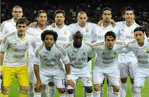"Real Madrid vs Malaga. The Real Madrid team show their support for fellow football players Eric Abidal and Fabrice Muamba; wearing ""Animo Abidal"" and ""Get Well Soon Muamba"" on their shirts. Muamba remains critically ill in the London Chest Hospital after suffering a cardiac arrest at White Hart Lane during Bolton's game against Tottenham on Saturday. Abidal meanwhile has undergone a liver transplant as he continues his recovery from a liver tumour."