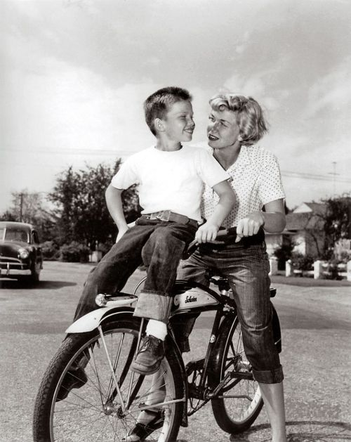 Doris Day and Terry Melcher ride a bike.