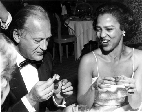 "Dorothy Dandridge and actor Curd Jürgens (her co-star in 1958's Tamango) enjoy hors d'oeuvres at a party thrown by producer Mike Todd (then-husband of Elizabeth Taylor) for his film ""Around the World in Eighty Days"" during the Cannes Film Festival in May 1957. Photo by Red Grandy, who has a great story about crashing the party to take this and other pictures."