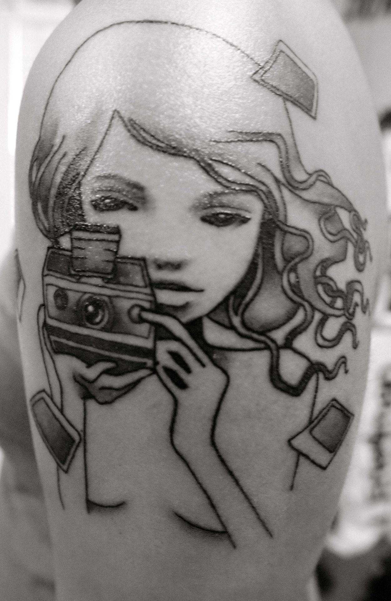 A tattoo of one of Audrey Kawasaki's pieces depicting a girl with a polaroid. Done by Jess V @ Sacred Tattoos in New York, NY.