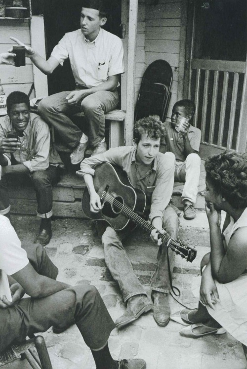 Bob Dylan plays on the back of the SNCC office in Greenwood, Mississippi, 1963