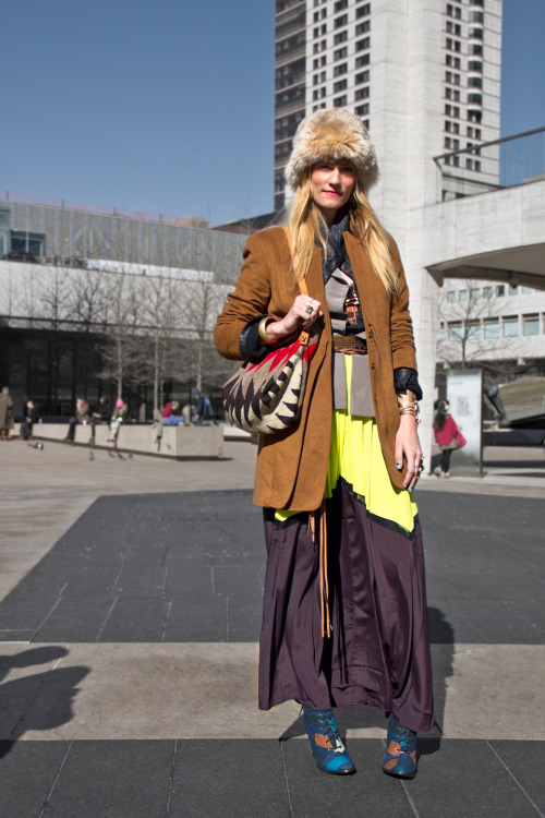 Designer Gretchen Jones photographed at Lincoln Center during #NYFW and carrying a custom bag by R+G made from an antique Navajo weaving, saddle leather, and leather cord. Excerpt from Runway to Streets: The intricately layered tops and outerwear, paired with the color-blocked skirt lend a more dimensional quality to the outfit. by Demian Lee