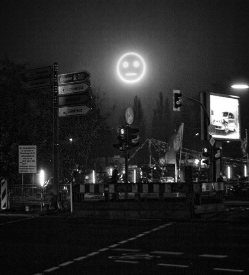 lagubeko:  via wired, via murmurandshout:  Public Face I is a giant neon smiley face mounted high over Berlin that uses analysis of the faces of people in the street to reflect the mood of the city in real-time. Creator Julius von Bismarck's current job title is, incredibly, artist-in-residence at CERN.