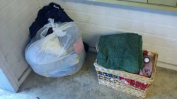 3/20/12 - Plastic bag full of clothes and a reem of copy paper, and a basket of assorted linens, books, and bath bubbles.