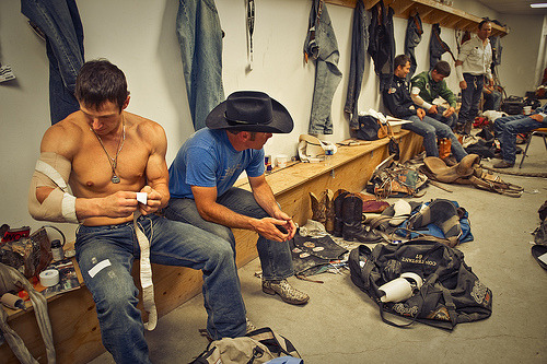 Locker room full of cowboys, jeans & sweat at a rodeo