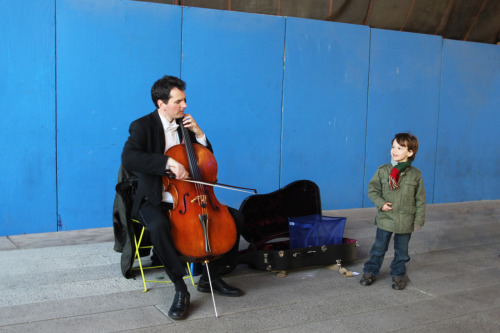 A boy listens to a cellist on the High Line.