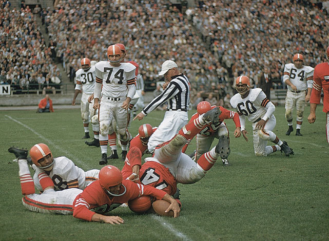 The referee marks the ball down as members of the Browns and 49ers scramble for possession during a 1956 game. The 49ers held on for a 28-17 victory. (Hy Peskin/SI) Credit: Hy Peskin SetNumber: X4022