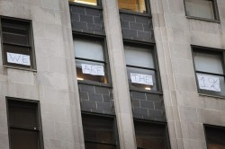 """WE ARE THE 1%"" - Chicago Traders ""Here's a look at the windows of the Chicago Board of Trade, in which a daring band of the nation's money people have fought back against the Occupy Chicago protest onslaught by declaring, ""We are the 1%,"" with some signs in the windows."" 10/5/2011 -Jim Newell via Gawker.com"