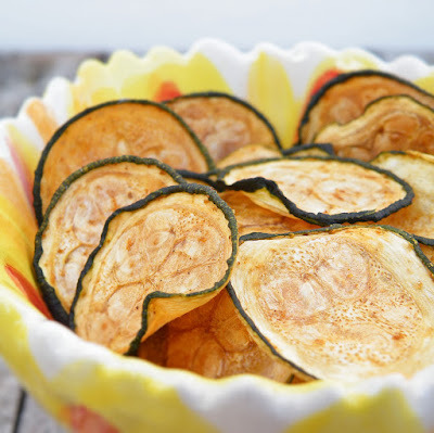 Baked Zucchini Chips  1 zucchini  canola cooking spray seasoned salt, or other seasoning(s) of your choice Preheat oven to 225 degrees.  Line a baking sheet with parchment paper or nonstick foil, and spray with canola oil.  Set aside.Slice zucchini into thin medallions, about the thickness of a quarter.  (You can either use a knife & a very steady hand, or a mandoline slicer.)Lay out slices on prepared baking sheet, and spray tops lightly with additional cooking spray.  Sprinkle with seasonings of your choice. (A note on seasoning, however - use LESS than what seems appropriate.  These shrink considerably in the oven, and if you use too much it gets very concentrated.  It's better to end up underseasoning and add more later.)Place in preheated oven and bake 45 minutes.  Rotate baking sheet, and bake an additional 30-50 minutes, until chips are browned and crisped to your liking.  These are best eaten within a couple hours of removing from the oven, as they start to get chewy if left out.  One zucchini makes one serving (1/4 C. - 1/3 C. of chips depending on the size of your squash).