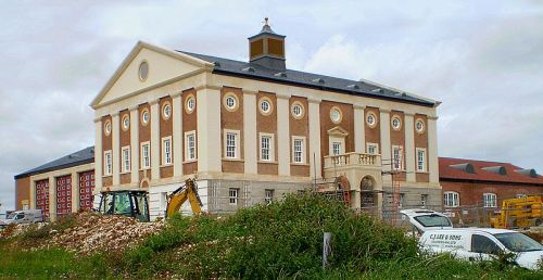 "Dorset Fire & Rescue Service HQ, Poundbury, Dorset  Prince Charles, the well-known critic of modern architecture has stuck his neck out in the last few years overseeing the construction of Poundbury, a village that tries to transplant the spirit of twee English villages into a brand new suburb of Dorchester. This particular building, a 2009 Carbuncle Cup nominee is the home of Dorset's fire service. Some time around a decade ago, after years of standing on the sidelines of the architectural community hissing and booing HRH decided to answer the question ""if you think you can do better why don't you?"". The result is a chintzy, ugly village in Dorset, a marriage of New Urbanism and strawberries and cream jingoism, a collection of architectural set-pieces where even the bus stops seem to have the hand of Windsor upon them, see (here). Poundbury comes across as a kind of architectural in-joke. It takes Charles' aesthetic ideals to their logical extremes and creates a kind of neo-Georgian playground for him and his fellow Mailites to wallow around in and complain about the rest of the country going to hell in a handcart. There's no architectural merit here, the kind of office blocks you can see (here) wouldn't look out of place on a Basingstoke office park and what isn't incredibly ugly is just a carbon-copy of vernacular buildings from elsewhere. What really riled me though is the building I mentioned before, the fire station. It's plain wrong, the proportions have nothing to do with Classical architecture and there is no detail that suggests any knowledge of classicism. Instead it is a stately home's stable block, it is a copy of a copy of a copy and as you'd expect it has all the subtlety, poise and elegance of a Duchy's Original scone dipped in honey and sprinkled with icing sugar. Not only does it look like something that would give Pevsner a heart attack but it's also a working building, there's three massive garage doors plumbed into the side and for the next few decades some poor firemen are going to have to live their lives through Prince Charles' experiment. It's just exasperatingly ugly and a massive middle finger to anyone who thought the Prince wouldn't be able to live out his dreams.  I guess he's got to keep himself busy somehow. He probably thought he'd be king by now."