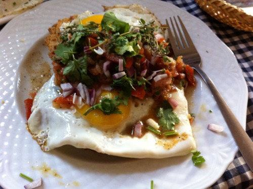 Huevos Rancheros in Berlin - 2 fried eggs on crispy corn tortillas, filled with black beans and cheese - topped with salsa.