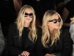 Mary Kate Olsen and Ashley Olsen in front row of a fashion show