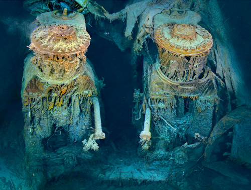 "kateoplis:  Two of Titanic's engines lie exposed in a gaping cross section of the stern. Draped in ""rusticles""—orange stalactites created by iron-eating bacteria—these massive structures, four stories tall, once powered the largest moving man-made object on Earth."