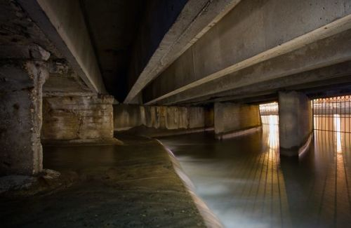 "11 Rivers Forced Underground… Today is World Water Day, and a good time to reflect on rivers, the lifeblood of many plant, animal, and human communities. Yet many of the world's rivers have been dammed, degraded, polluted, and overdrawn at alarming rates. Some of the world's great rivers, from the Colorado to the Indus, don't always reach their ends because people have diverted so much water for agriculture, industry, and municipal uses. Other rivers have been completely covered over by development, as people attempted to ""tame"" nature by ending flooding and maximizing usable land area. But what happens to once-thriving freshwater ecosystems when the rivers they depend on are entombed in sewer pipes beneath layers of concrete and soil? Few species can make the transition to subterranean living. Ironically, it was often rivers and streams that attracted people in the first place, but those very sources of life can fall victim to the expanding concrete jungle. This was the case in the late 1800s for Sunswick Creek in the Queens section of New York City. Appearing on maps in the 1870s, Sunswick Creek was soon completely covered over. Now, it exists only as a meager flow through buried sewer-like pipes, as documented in this photo by Steve Duncan. Duncan notes that the burial process appears to have occurred in multiple phases, based on his explorations of the dank channels. —Brian Clark Howard"