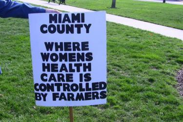 "Cuts to Title X? The Women of Miami County, Kansas Already Know What That Means by Kari Ann Rinker  The stated intent of eviscerating Title X has been to divert funding to local health departments. Proponents stated that the contraceptive needs of low-income women can be satisfactorily met through these providers. For the women of Miami County, Kansas, that theory is already proving false. They've already experienced the cuts and been denied access to affordable contraception, as the result of a 3 to 2 vote by Miami County Commissioners to decline Title X money from the state. […] One person held a sign that read ""Miami County, where women's health care is controlled by farmers.""  The sign was commentary about Miami County Commissioner Pretz, who received $85,000 in farm subsidies… you know…""government money.""  Mr. Pretz cast a vote declining the Title X funds stating that he doesn't believe taxpayers should be paying for contraceptives to be given out at the health department."