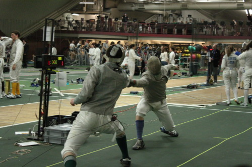 modernfencing:  [ID: two sabre fencers, in a bout. The one on the right is lunging and hitting his opponent.] James Kiefner (right)! A cool guy and a great sabre fencer. (Photo by Nicole Chan.)  Kiefner is on my fencing team in college!