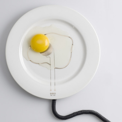 "DESIGN GENIOUS!! What a great design to keep your food hot whilst eating, or even cooking some ingredients straight on your plate! There's nothing like food practicality. Ok, maybe the idea of having all sorts of cords in your kitchen, at the dinner table, isn't what you would like most, but come on! This is too good to be true! Designer Ami Drach & Dov Ganchrow came up the ""+/- hot plate"". They silk-screened gold or Amorphic Metal films onto ceramic plates. If you connect the to an electric source, the current will run through the pattern on the plate and keep the food warm."