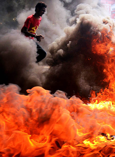 Makasar, Indonesia: A man runs through burning tires during student protests against the goverment´s plans to raise fuel prices. via frameworkla