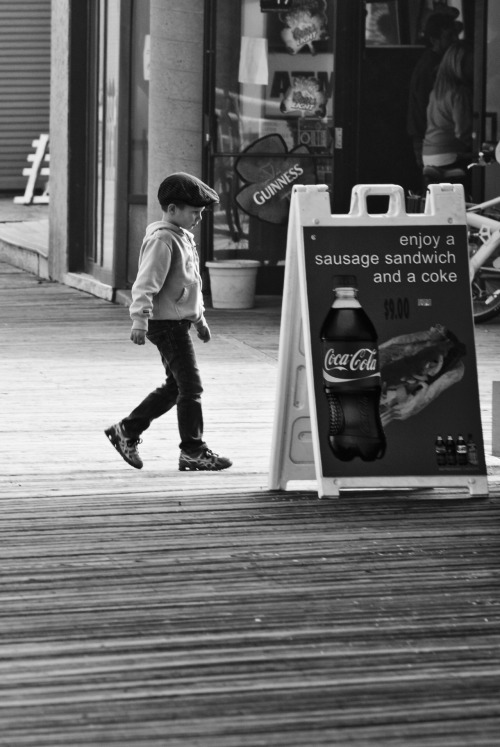 Seaside Boardwalk Kid - New Jersey This is another photo I took at Seaside.  As previously mentioned, it was a very foggy day at the board walk, but I was lucky enough for a few moments of sun to capture this image where the kid was framed right in the light.  Unfortunately I was further away than I would have like to of been and had to crop the image to get the composition I wanted.  I also only had moments to get the image so I did not have enough time to adjust my settings and get less detail on the background to put emphasis on the kid.