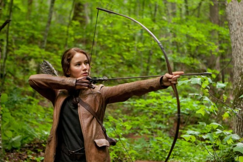 The Hunger Games, a highly-anticipated adaptation that almost lives up to the hype Last night, I had the distinct pleasure of seeing The Hunger Games at midnight. Oh boy. If any of you ever thought the Harry Potter crowd was interesting, you've never seen a Hunger Games crowd. Anyways, onto the review.  I admit that film adaptations of cherished books are never an easy feat. The fan expectations would make any director curl up into a ball with anxiety. Yet, Gary Ross did a stellar job, despite my initial apprehensions (his previous directorial endeavors include Pleansantville and Seabiscuit!!). What I liked most about Ross's directing is that he showed most of the time instead of telling, and for an adaptation of a book that is written in first person narrative I think that choice was quite smart. While there are scenes that I definitely imaged differently in my head, the emotions that the film evoked were the same as the much-beloved novel.  One of the main reasons I loved Katniss was because she was a fantastic female character that young girls could look up to. She wasn't madly in love with her boyfriend, nor did she turn into a whimpering mess when he left her. Instead she was strong, brave, selfless and truly multi-dimensional. The casting of Jennifer Lawrence, in my opinion, was perfect. Despite the blonde hair, I knew she would be a superb Katniss, especially after seeing her in Winter's Bone. Overall, I think the cast was great: Stanley Tucci was flawless as always; Liam Hemsworth was better than I expected; Josh Hutcherson was adorable, but I didn't quite always believe the chemistry between he and Katniss; and I'm still not crazy about Lenny Kravitz as Cinna—I just don't think he was coolheaded and mysterious enough in this role, but that could also be partly the lack of time to fully develop his character and his relationship with Katniss in the film.   There is so much more to say, but I'll keep it brief. The production values could have been a bit better in regards to the costumes. For a multi-million dollar film, I thought the costumes and special effects looked a tad cheesy (and what was up with that cornucopia?!). I will give the film credit for its pacing. It managed to hit all the important points in record time and I quite enjoyed seeing Seneca Crane, the Head Gamemaker, have a much larger role in the film. It was interesting to see the behind-the-scenes of the Hunger Games because in the books we only see as much as Katniss does. I'm glad Ross and fellow screenwriters Suzanne Collins and Billy Ray decided to include that.  Overall, as a fan, I enjoyed myself. As an impartial cinephile, I think the film had some great cinematic qualities. It's definitely still popcorn, but very mature and visually-striking popcorn. Did any of you all go see it at midnight? Any of you going tonight?