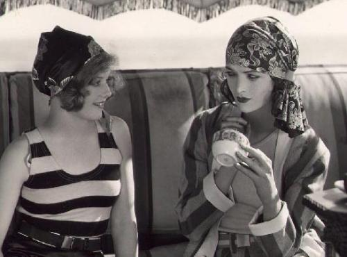 silentcuriosity:  Seaside flappers Agnes Franey and Myrna Loy show off the latest 1929 beach fashions.