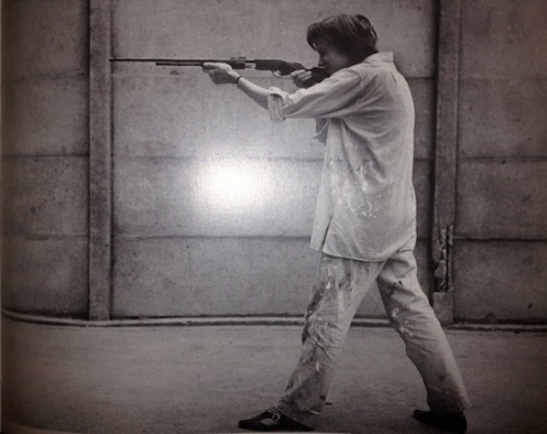 "Niki de Saint Phalle shooting with a .22 rifle in the Impasse Ronsin, Paris, 1961. ""As victims, I choose my paintings,"" said French artist Niki de Saint Phalle, who would suspend balloons of paint or beer cans from her artwork and shoot at them. The bullets would splatter the paint and puncture canvases. Shunk-Kender, © Lichtenstein Foundation"