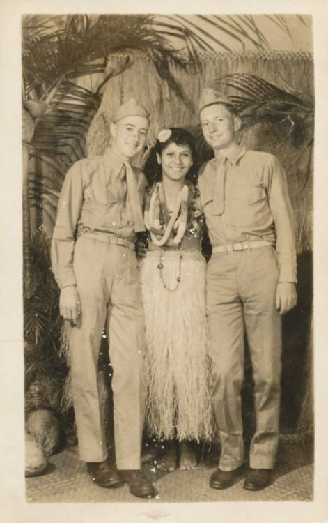 "Souvenir photo of 2 young servicemen with hula girl against a ""native"" backdrop"