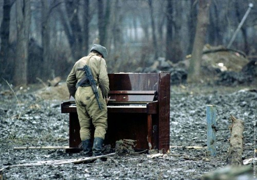 Russian soldier playing an abandoned piano, date unknown