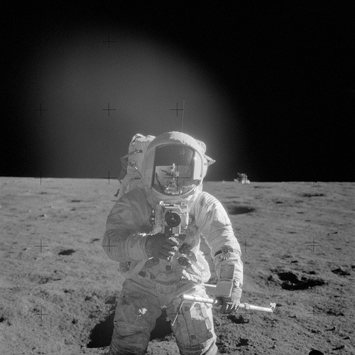 Astronaut Charles Conrad Jr., Apollo 12 commander, using a 70mm handheld Haselblad camera modified for lunar surface usage. (via NASA)