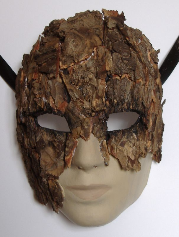 A somewhat better photo of the progress on the oak-bark mask, taken in natural light. This morning I've added a little black around the eye holes, just to subtly delineate/highlight them. Next steps are: carefully paint all the bits of white wood glue that are visible in a bark-colour, and paint up the non-bark areas (mouth, nose and chin) as bare wood.