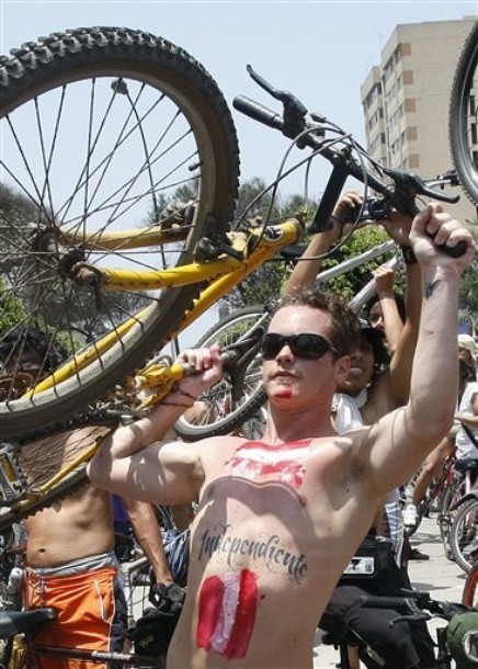 "Hundreds of nude and semi-nude cyclists demanding that authorities stop the hostilities bicyclists face from motorists, hold up their bikes in unison at the start of their ""Naked Bike,"" protest in Lima, Peru, Saturday March 10, 2012. This is the seventh consecutive year of the annual protest in which cyclists take to the streets in Lima to bring attention to the unsafe conditions for cyclists in the Peruvian capital. (via Photo from AP Photo)"
