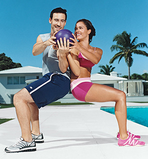 Partner Squats: A Hysterical Challenge This is a wicked bootcamp move I use often with my students! It's a tougher variation of the wall sit: having a partner makes it more challenging to find & keep your balance. Today: find someone close to your height, and give it a try! Tips:  Go back to back first, then slowly lower down & walk your feet out until you're in a squat. Use each other for balance, but place your weight in the heels of your feet. Try to be a 'wall' for your partner. The more planted & stable you are, the easier it is on your quads.  Keep your core tight!  Once you have the basic partner squat down, pass a ball (or a weight) from side to side, without breaking your squat. This will challenge your core: keep your hips facing forward and twist through the torso as you pass. Do 20 reps one way, and 20 the other. You can also pass it overhead and/or between your legs.