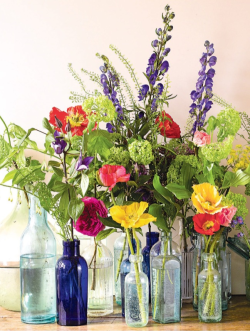 Beautiful flower arrangement using old bottles. UK Country Living