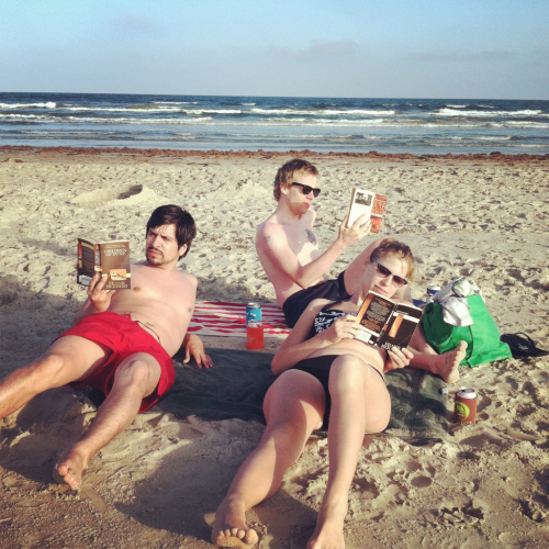 Three sexy people reading the first three of the series, on the beach!