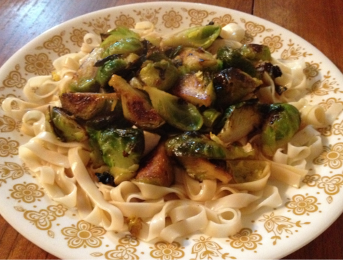 Tangy Udon Noodles with Lemon Honey Brussel Sprouts For this meal I used the same method for the Brussels as a recipe I posted earlier (Lemon honey sautéed Brussel sprouts, about a month ago) topped on wide udon noodles, which you can find at most natural food, Asian markets or some grocery stores. I flavored the noodles with my favorite combo of soy sauce, rice vinegar and lemon juice. For some extra protein add cubes of tofu or cooked soybeans. Ingredients: Wide udon noodles Brussel sprouts Rice vinegar Soy sauce  Lemon  Honey or vegan sweetener  Olive oil  Salt, pepper and garlic to taste  Directions: For the Brussels Boil a pot of water (with enough water to cover brussels) Wash brussels well, peeling off outer leaves if they look gross Chop into halves or quarters, depending on their size Put brussels into boiling water and cook for about 3-5 minutes, or until they are pretty cooked but still a little hard Strain and put brussels in a large pan with olive oil Add lemon juice, honey and herbs to taste (it tend to take a good amount of lemon and honey to be flavorful enough)  Continue to sautee until they are tender For the noodles:  Follow directions on the package to cook noodles  Drain and mix in a bowl with rice vinegar, soy sauce and lemon to taste.  Add protein source if desired and top with cooked Brussels. Enjoy :)